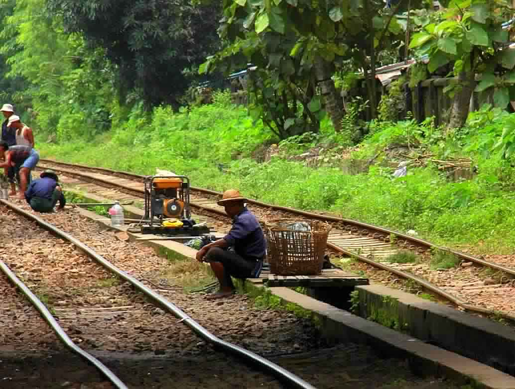 Workers rest for the afternoon at Yangon train tracks