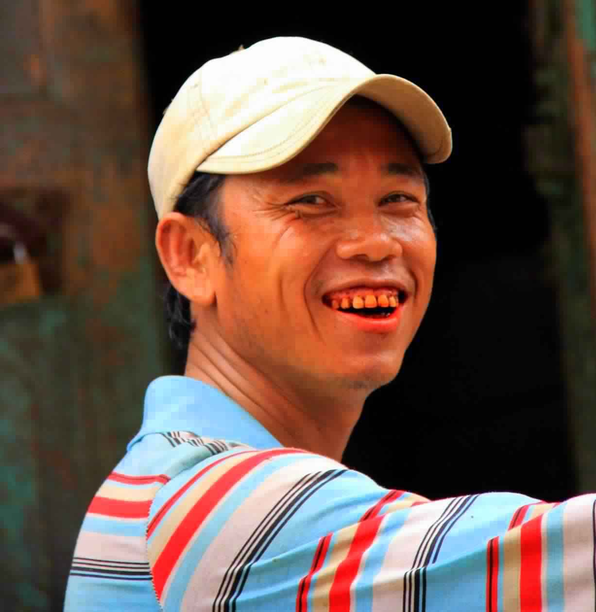 A young man proudly shows off his red stained teeth in Yangon