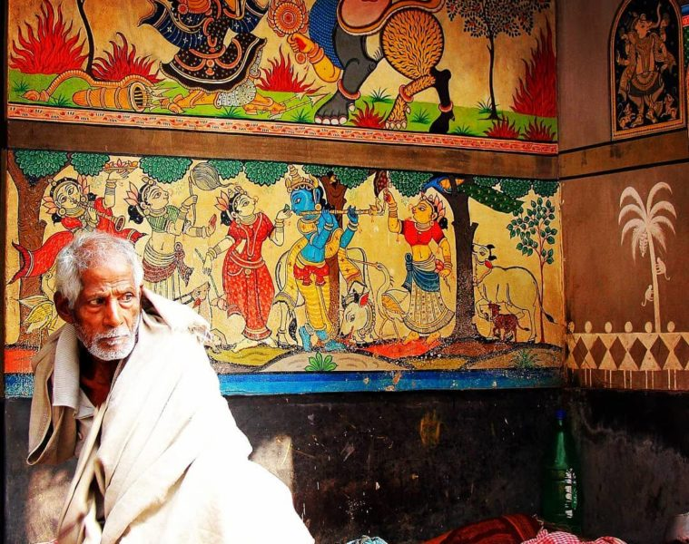 A man sits in front of his studio in raghurajpur