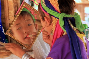 A little girl from the thai hill tribes applying make-up