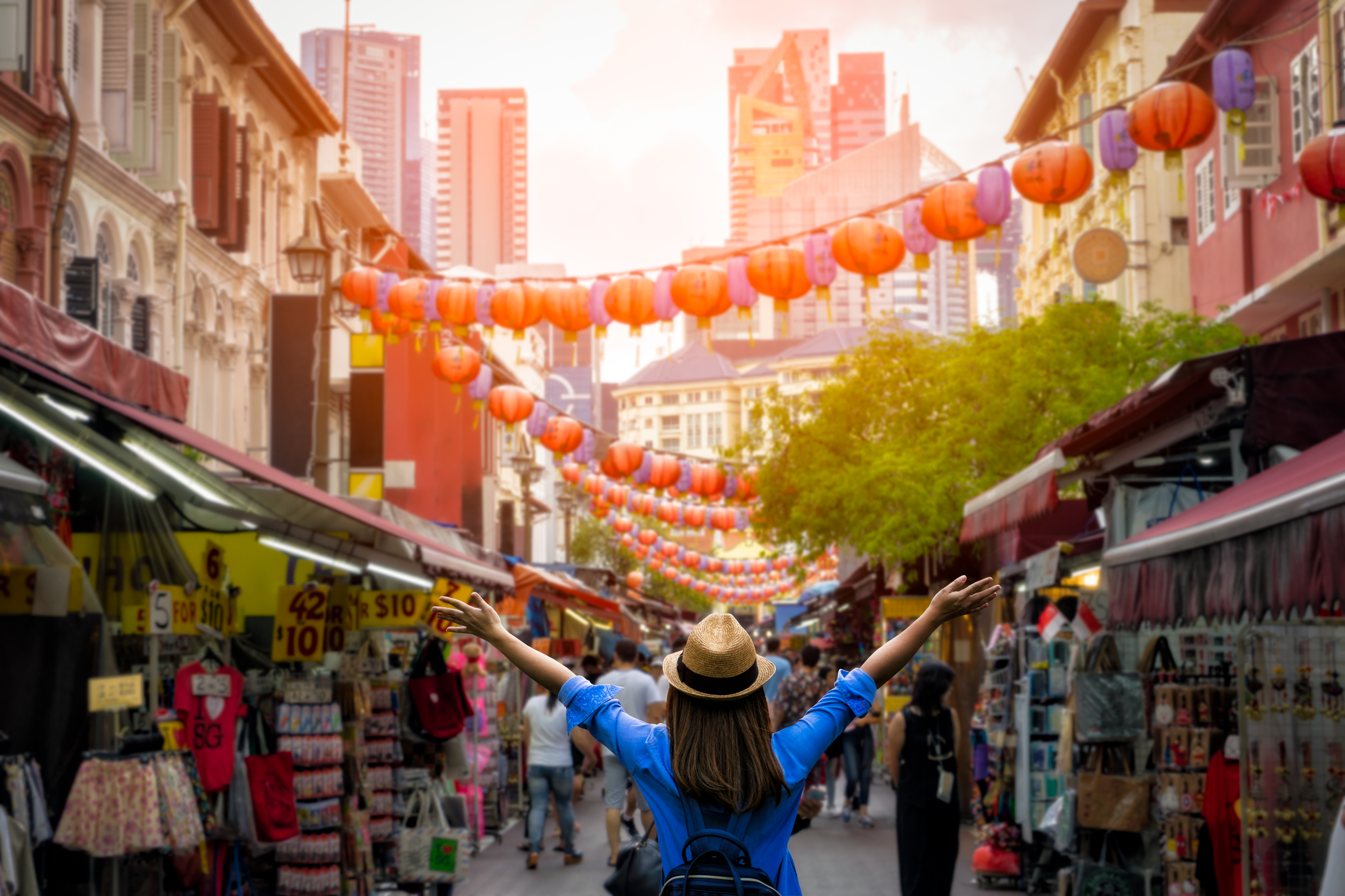 Young woman traveler with backpack and hat traveling into Chinatown at singapore city downtown. Travelling in Singapore concept